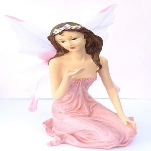 Winged Pink and White Fairy Sitting Holding a Small Flower in Her Hand
